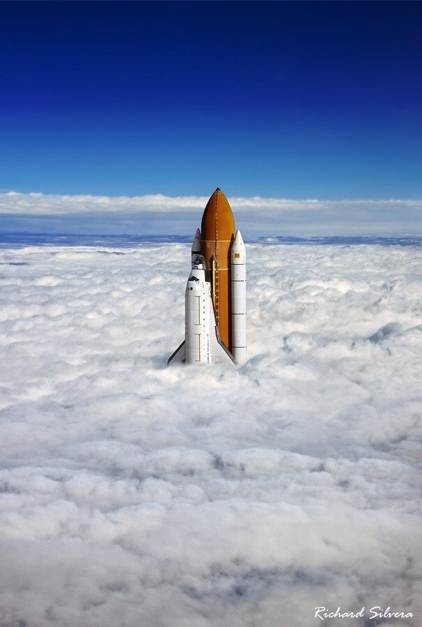 this space shuttle breaching the clouds